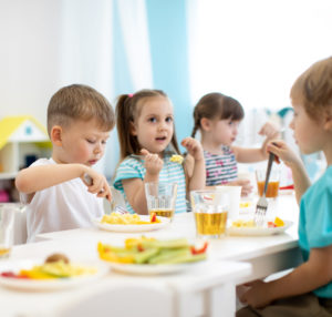 Group of preschool kids have a lunch in daycare. Children eating healthy food.