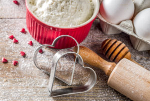 The tools to make valentine cookies are gathered together, flour in a red ramkin, eggs in an egg carton, two heart shaped cookie cutters and a rolling pin.