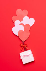 Valentines heart shapes in red and pink glued like balloons on a red background