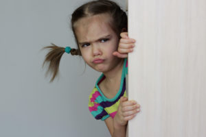 A pouting young girl in pigtails peeks around from behind a door.