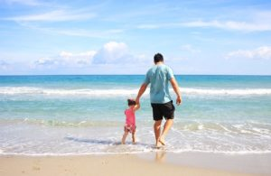 a father and his daughter walk along the water's edge on a sandy beach with blue sky and turquoise water in the background