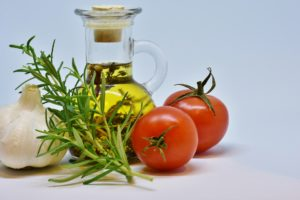 Still life of a bottle of olive oil surrounded by two red tomatoes, a sprig of green rosemary and a garlic bulb.